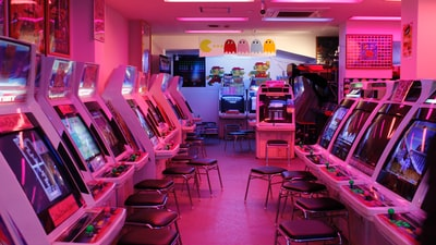 turned-on arcade machines with stools arcade teams background