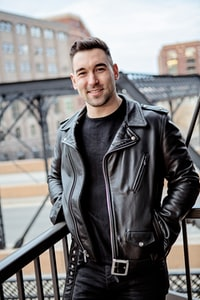 handsome smiling man in black leather jacket in front of city bridge