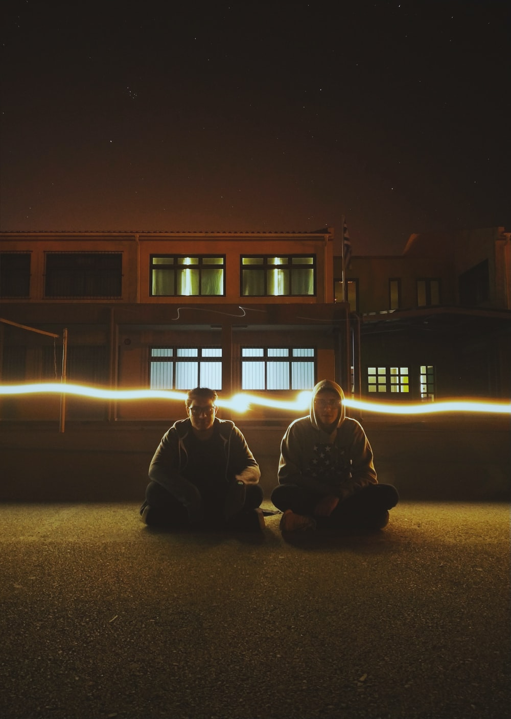 two man sitting on road