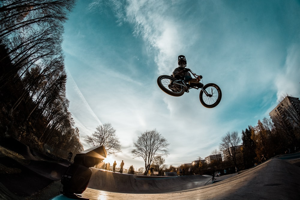 low-angle photography of person riding a bmx bike