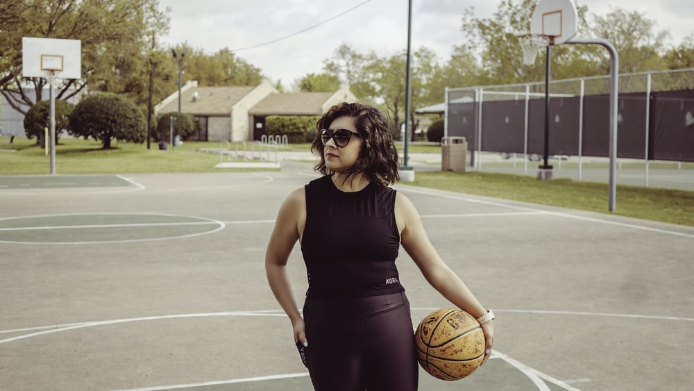 woman standing outdoors holding basketball