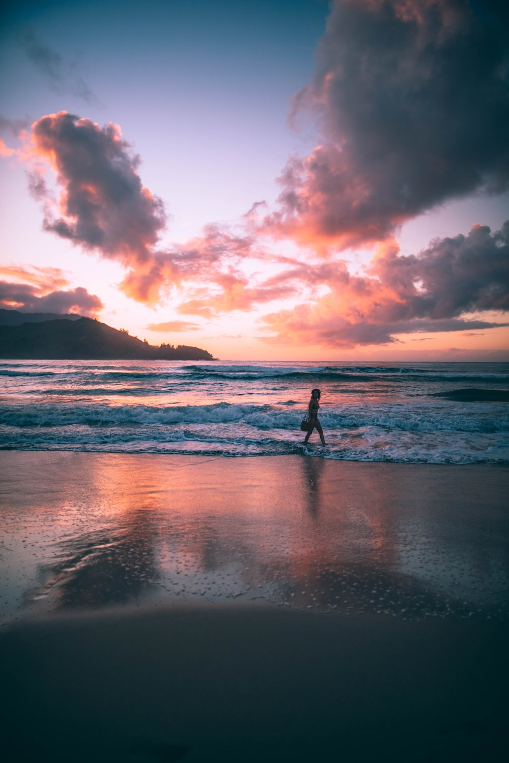 woman standing on sea waves during golden hour