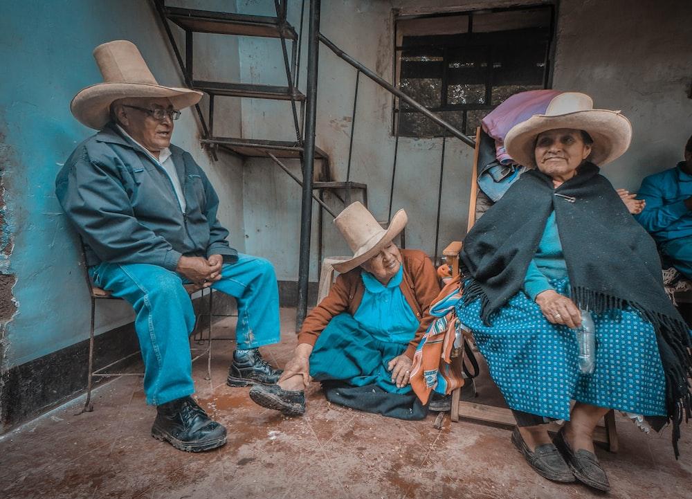 three person sitting near staircase