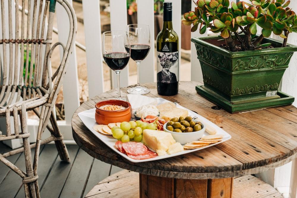 two wine glasses beside wine bottle on top of brown wooden reel table
