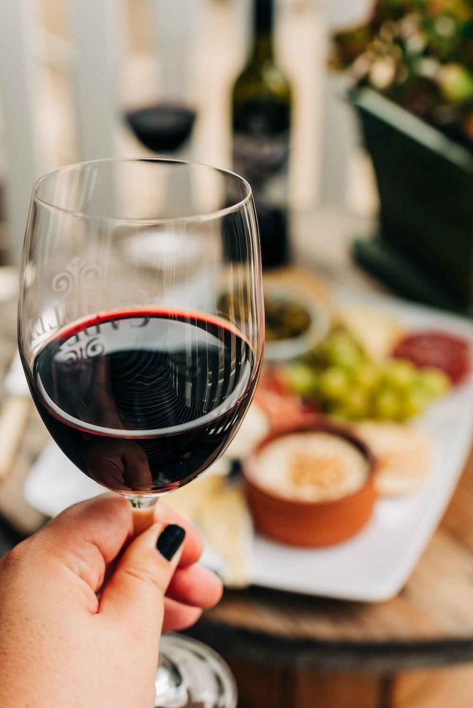 person holding half empty wine glass near table