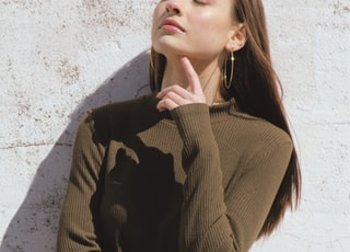 woman holding chin during daytime