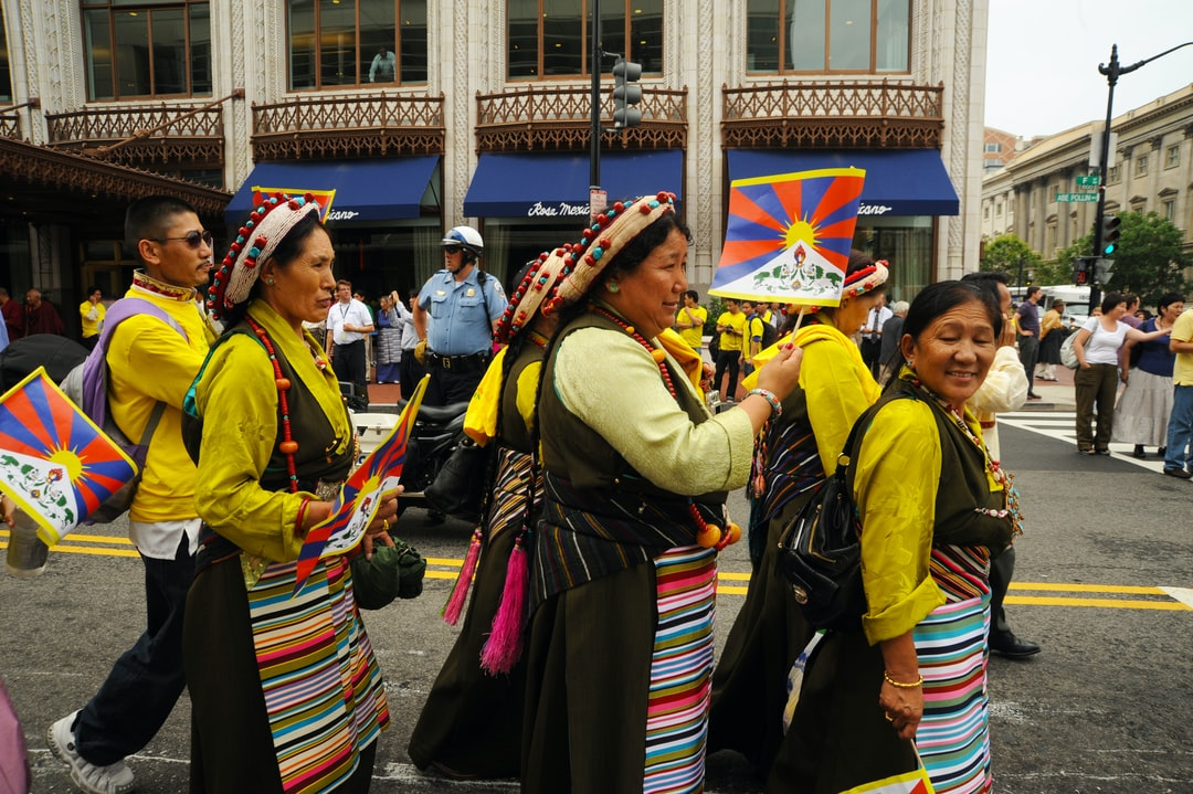 Tibetan women wearing traditional chubas, aprons, headgear of pearls, coral, turquoise, tassels, Tibetan Flag, police, His Holiness the Great 14th Dalai Lama Birthday Peace Parade, Kalachakra, Washington D.C., USA