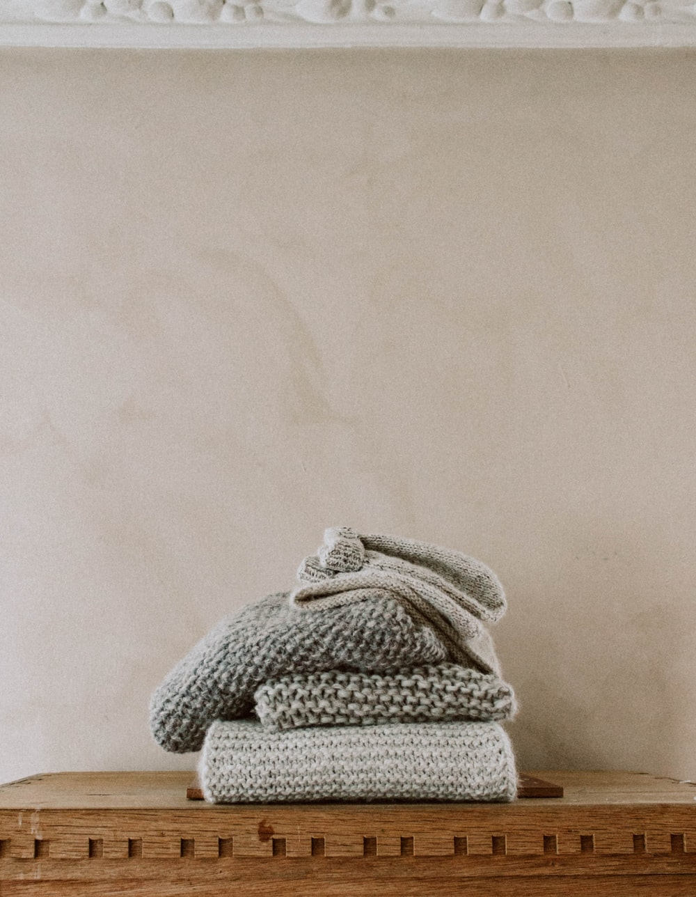 three grey knit textiles on brown wooden surface