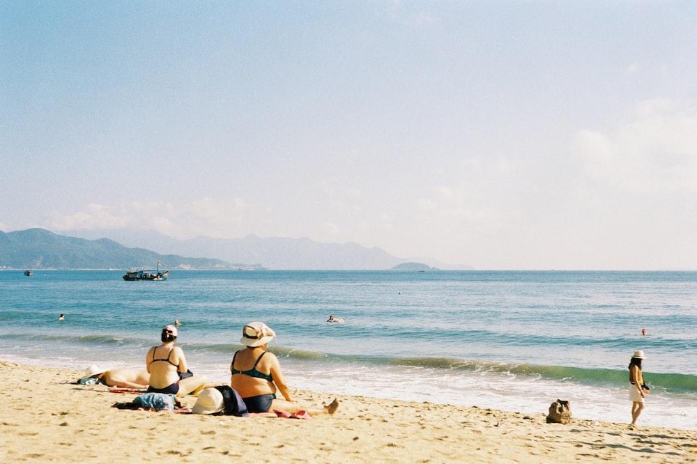 people sitting on seashore
