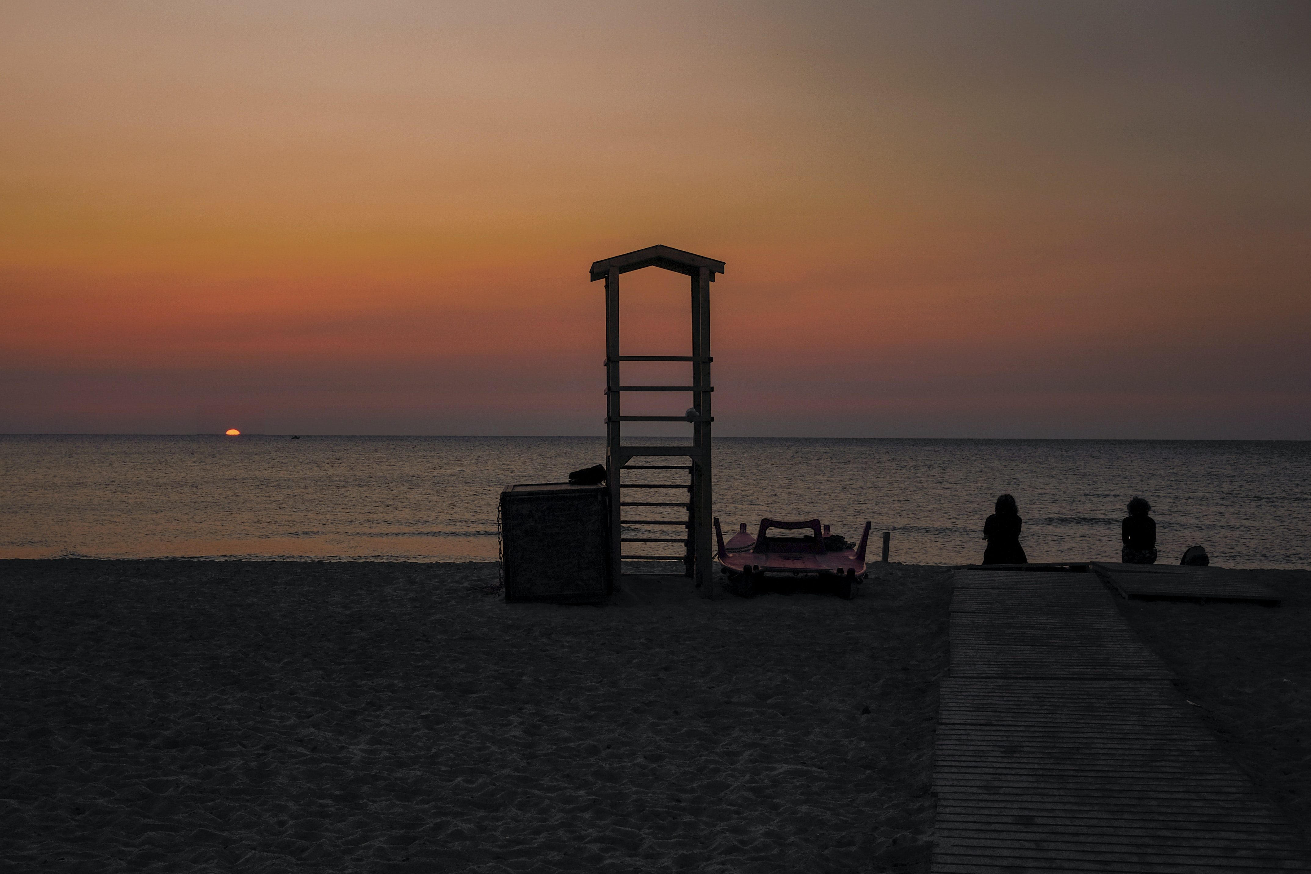 silhouette of two people sitting near the sea during sunset