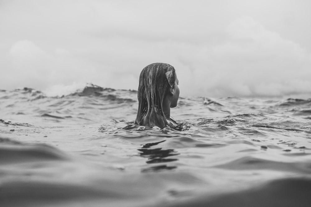 grayscale photography of woman in water during daytime