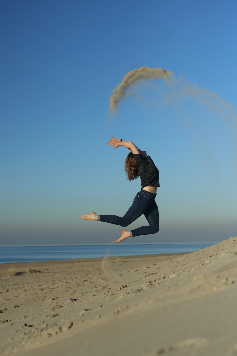 woman jumping on shore during daytime