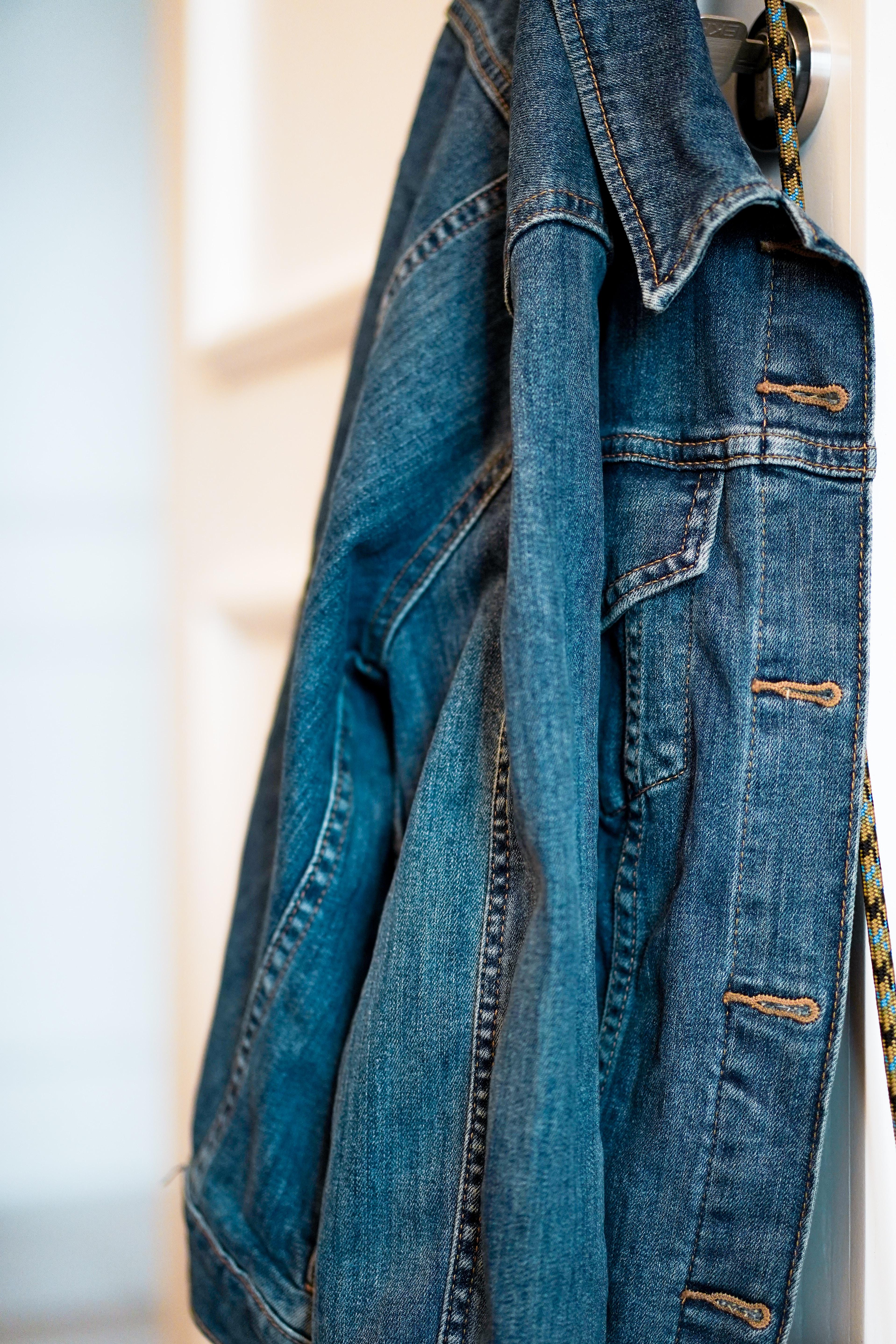 blue denim jacket hanging on wall