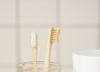 two brown wooden toothbrushes