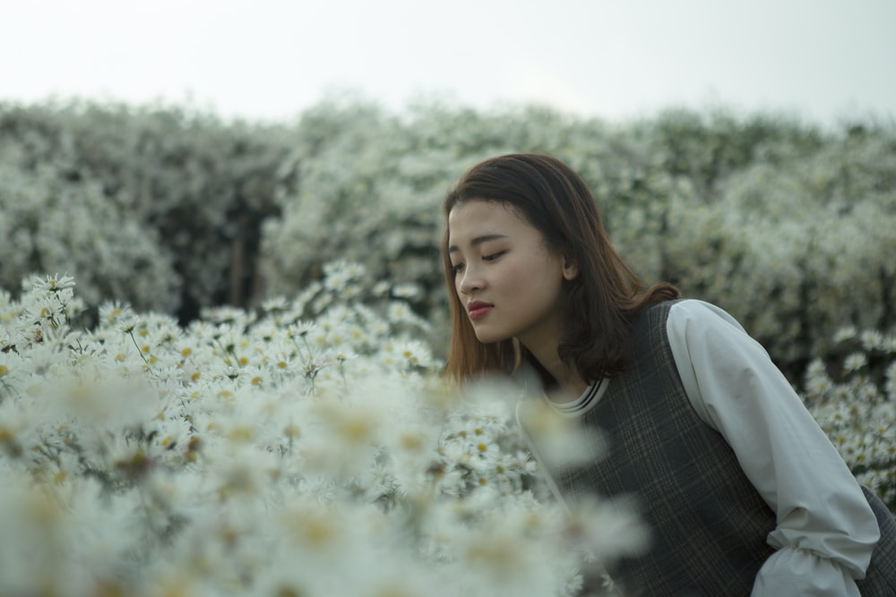 woman in white and gray long-sleeved top on flower field