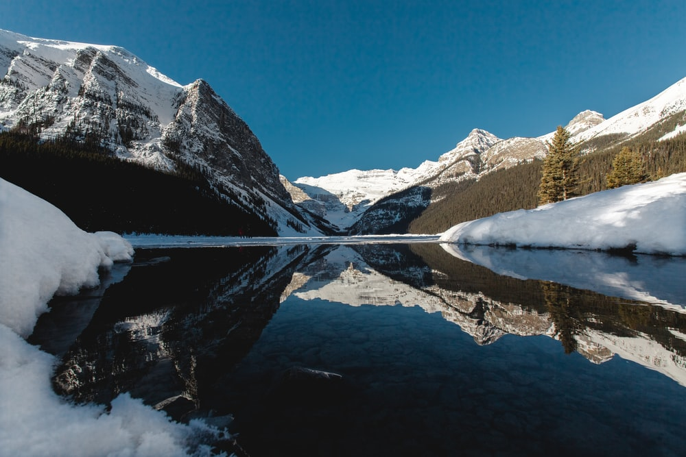 low angle photography of mountain near body of water
