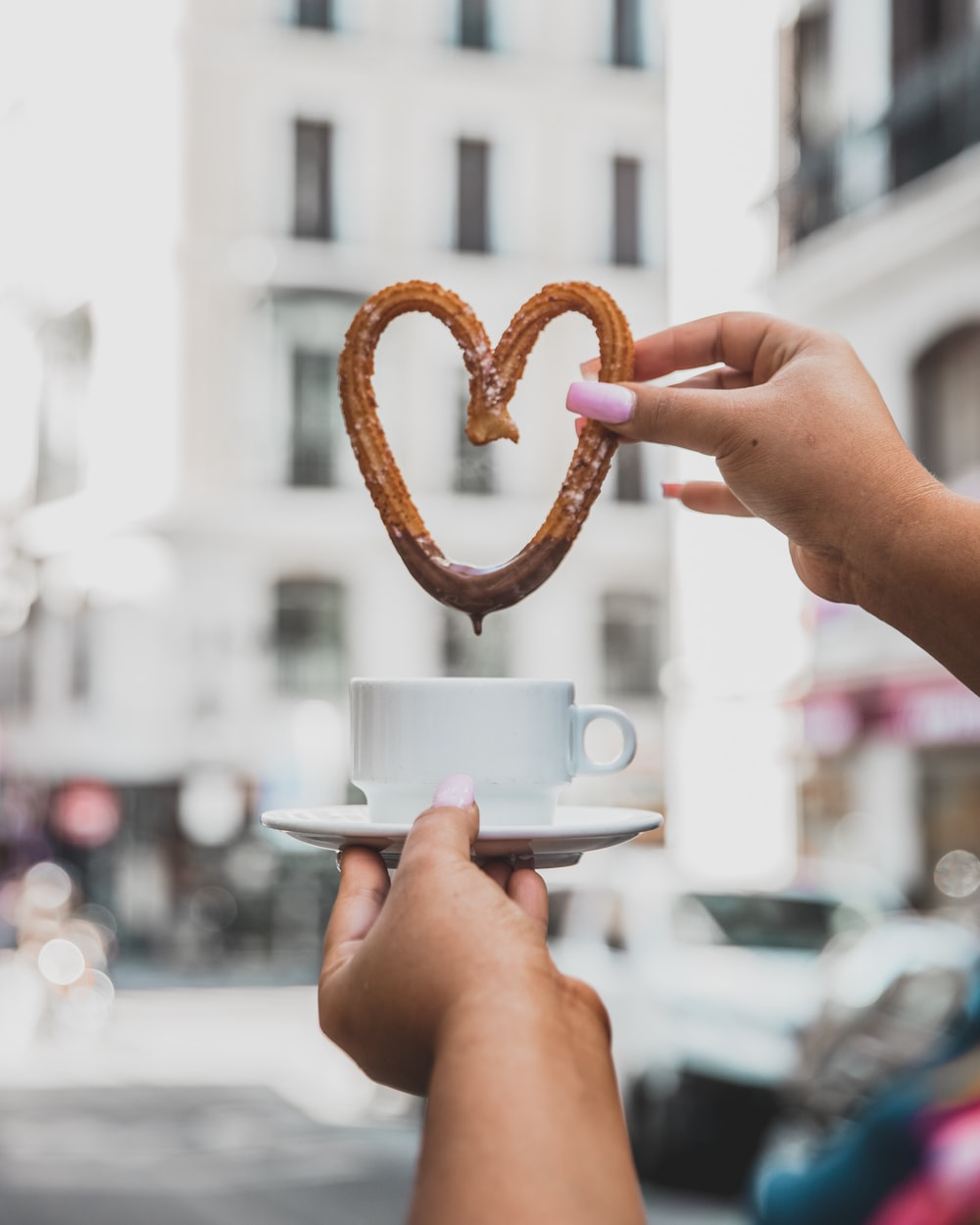 person holding teacup and churros