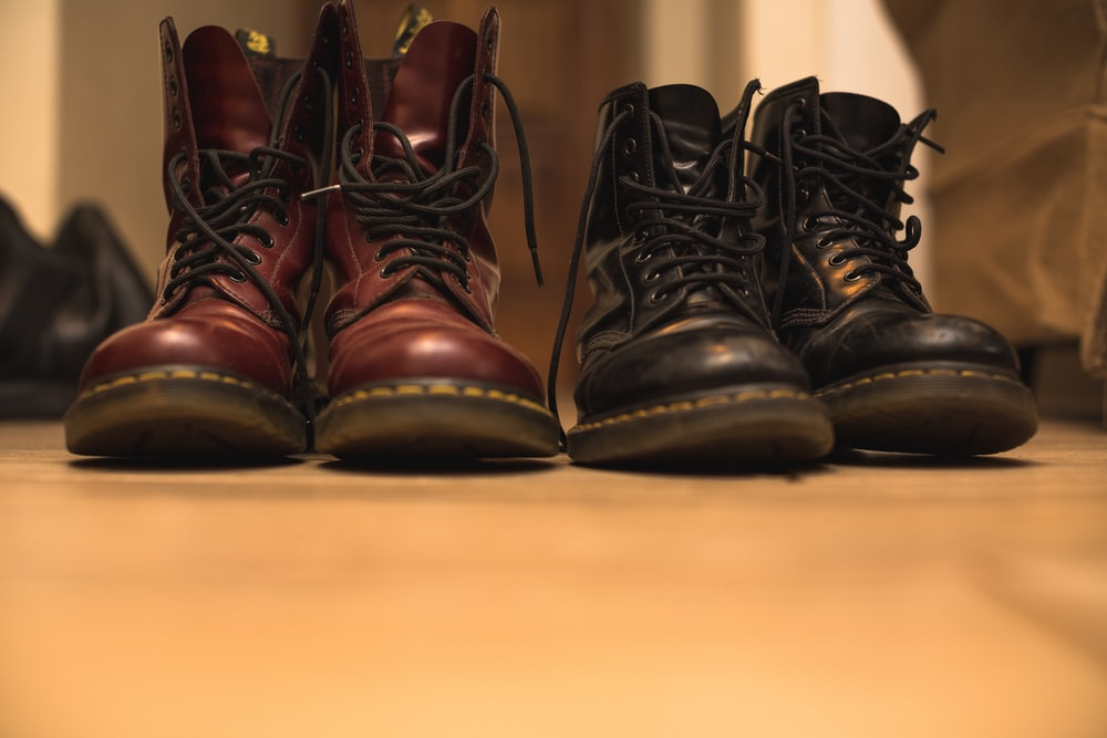 two pair of black and brown leather work boots on brown surface