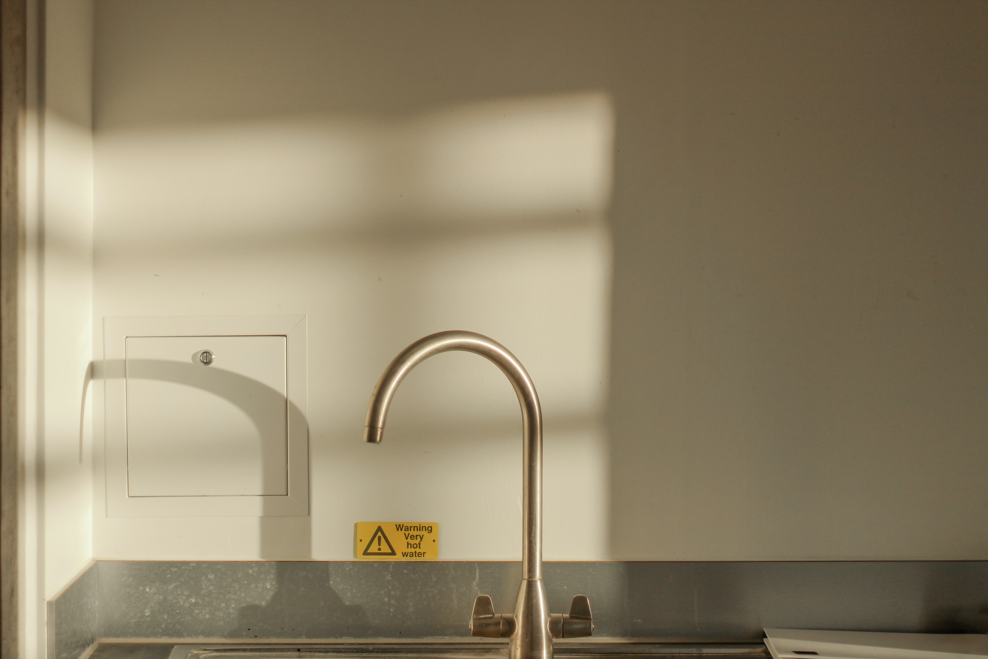 turned off faucet on sink with shadow on wall