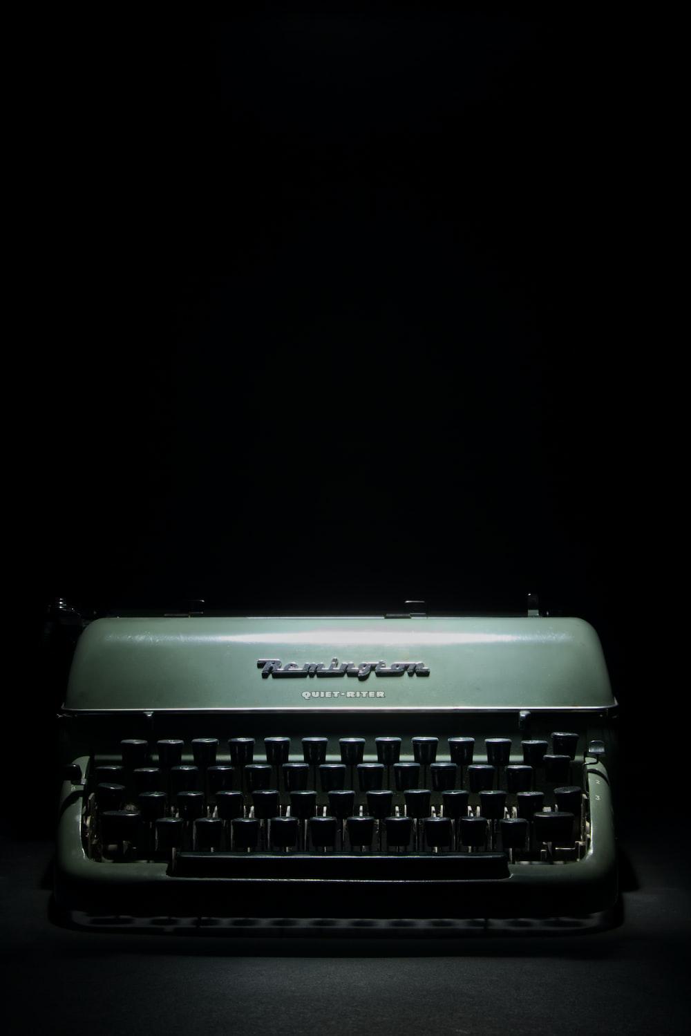 gray and black typewriter on black background