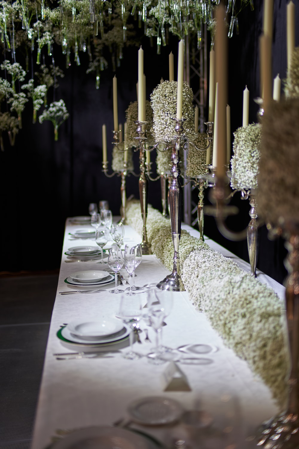 flower centerpieces, candles, and dinnerware set arrangement on table
