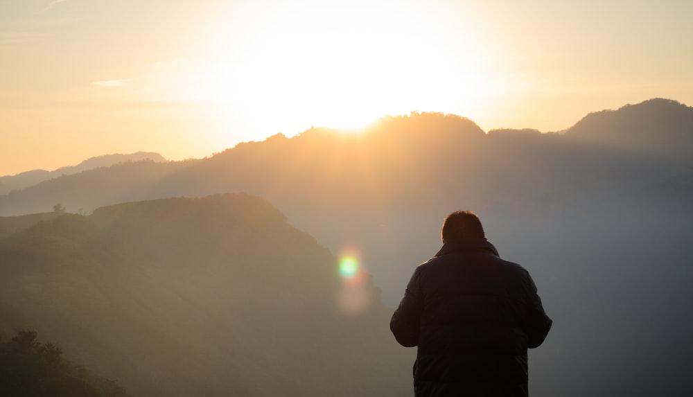 man standing facing at mountain