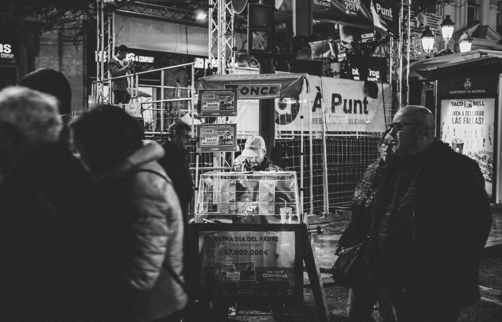 grayscale photography of man and woman walking side by side near stall
