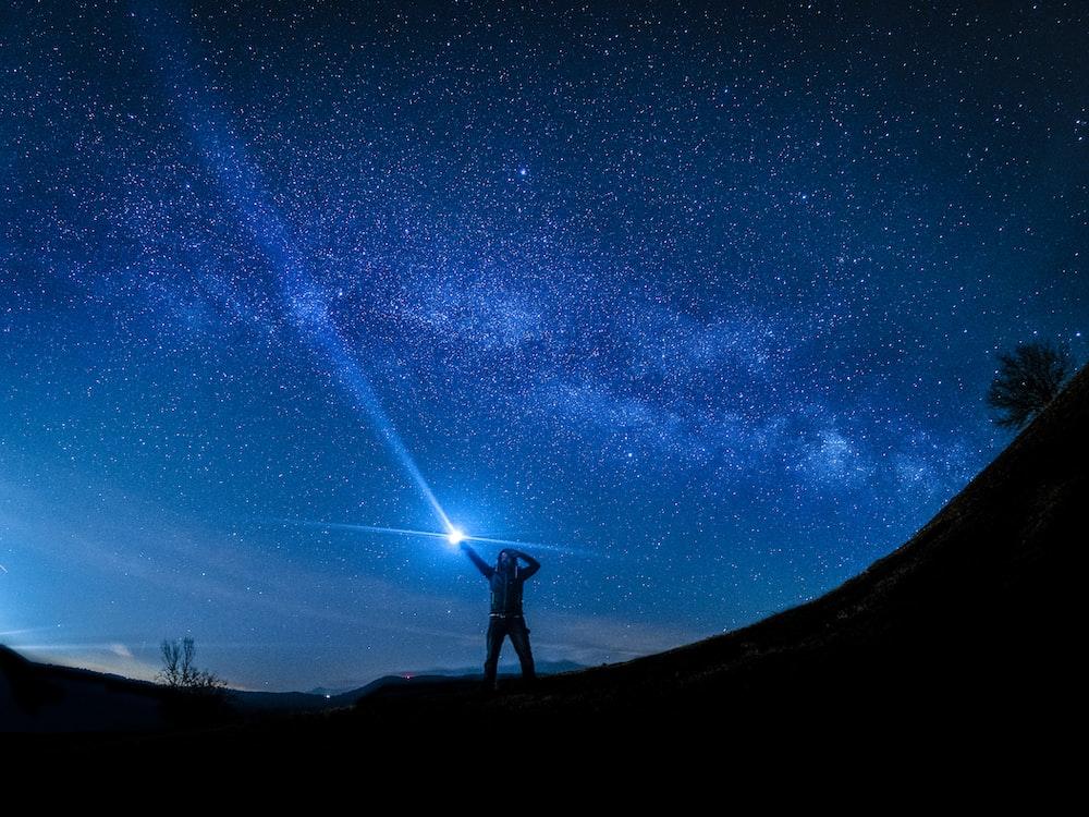 silhouette of man holding flashlight