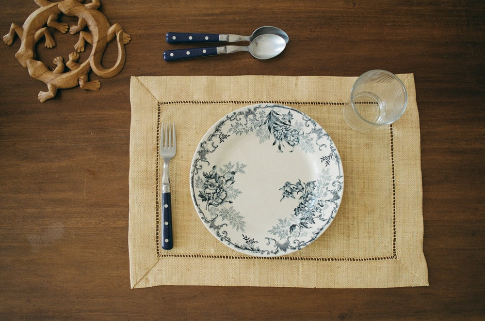 round white and gray plate and fork on brown placemat