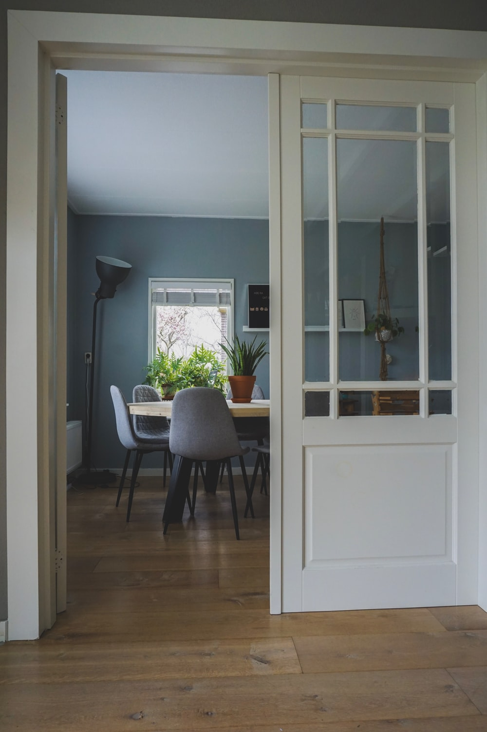 opened white wooden door through room with table and chairs