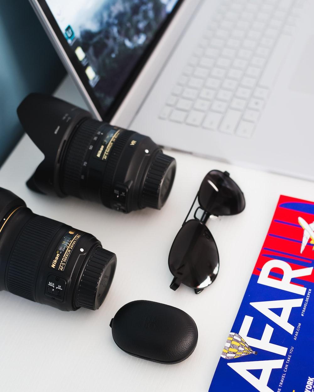 two black zoom lenses, black sunglasses, and black case beside white laptop computer