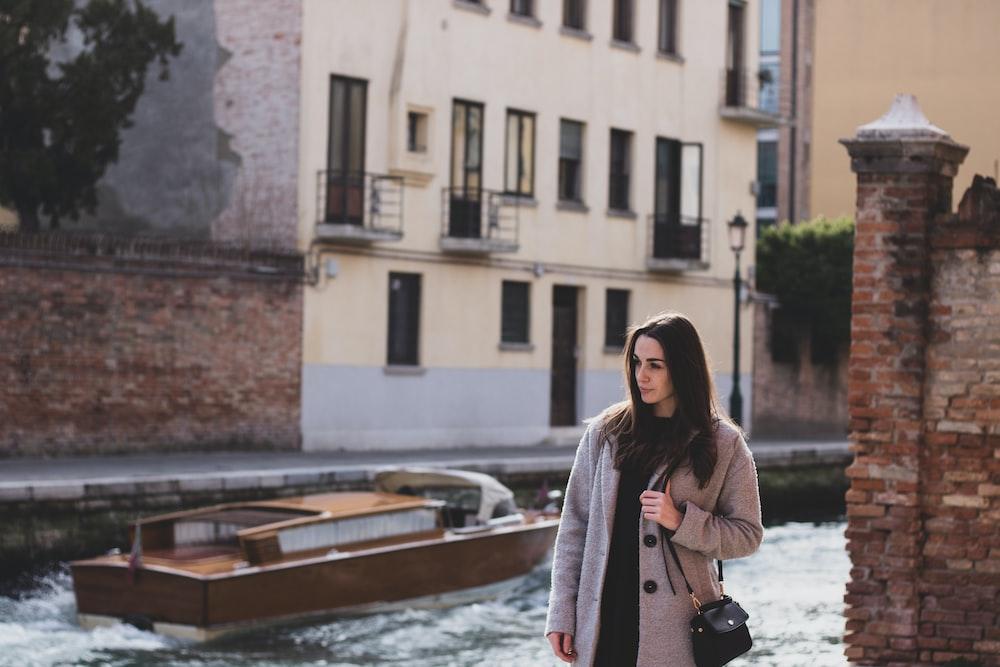 woman standing beside brown concrete brick wall