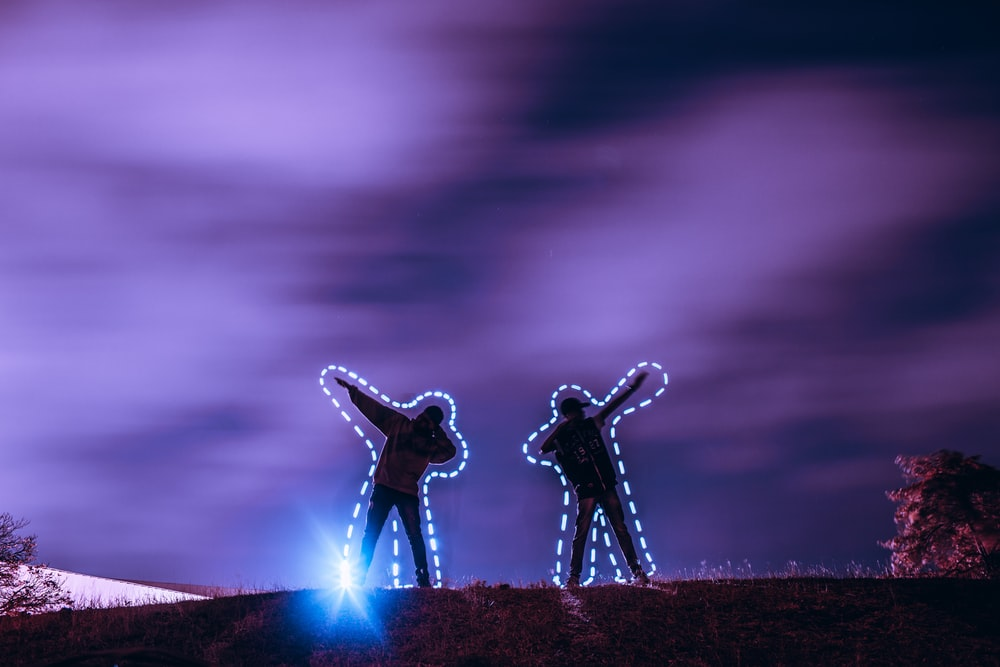 silhouette of two men standing and raising arms on their side