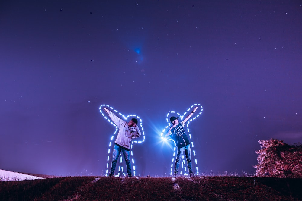 two men standing on hill under starry sky