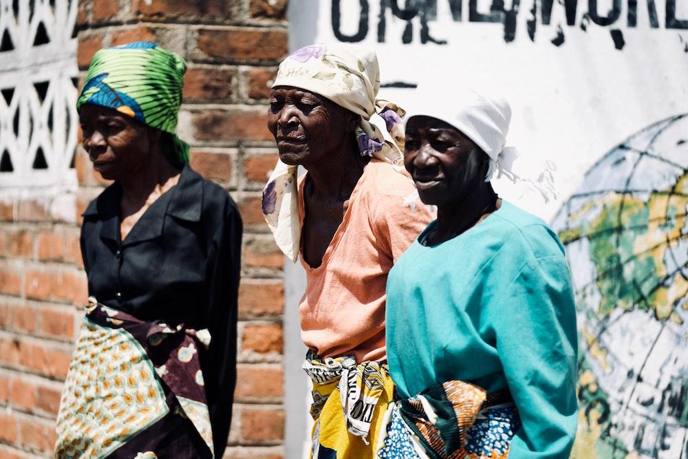 three women standing near wall