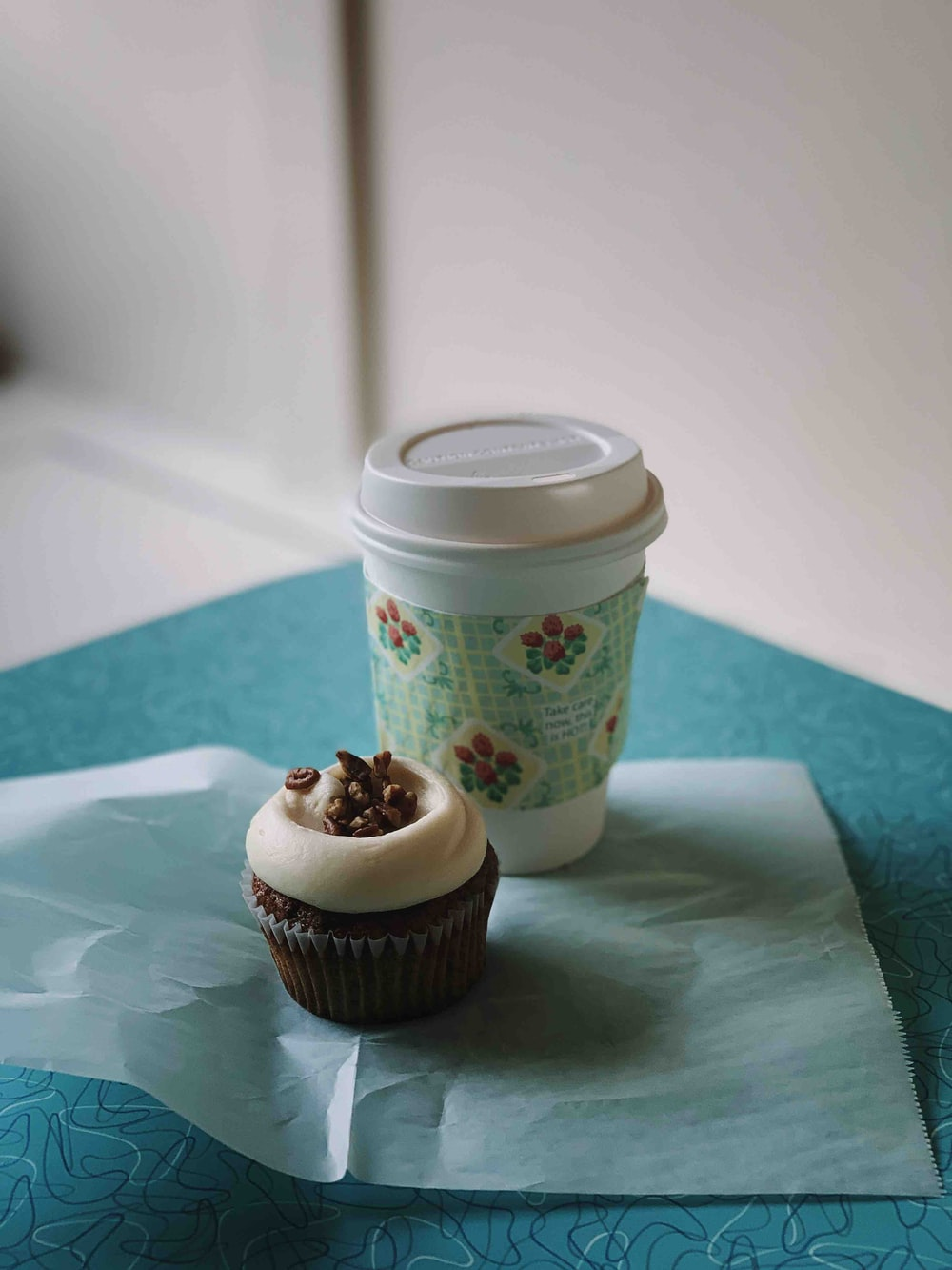 white and blue disposable cup beside chocolate cupcake