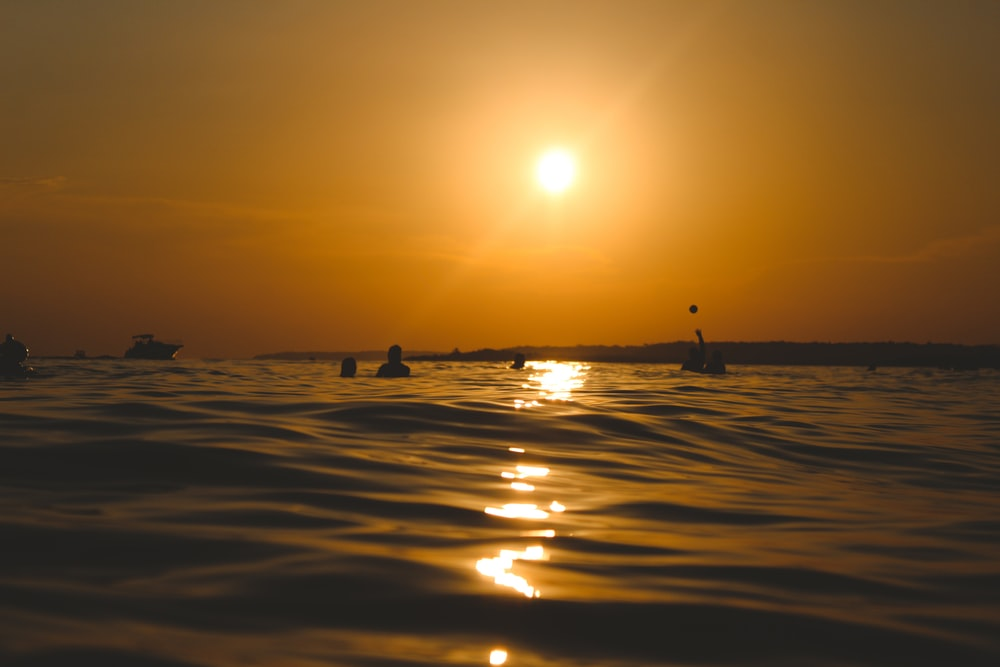 peopled bathing on sea during golden hour