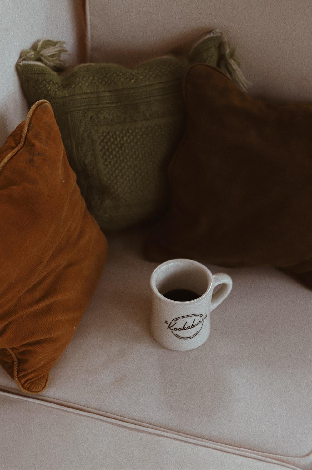 white ceramic mug near three assorted-color throw pillows