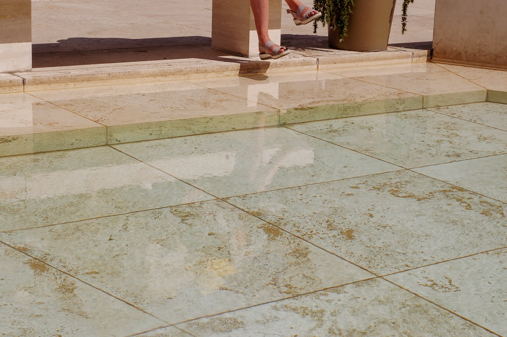 person standing on brown and white ceramic floor tiles