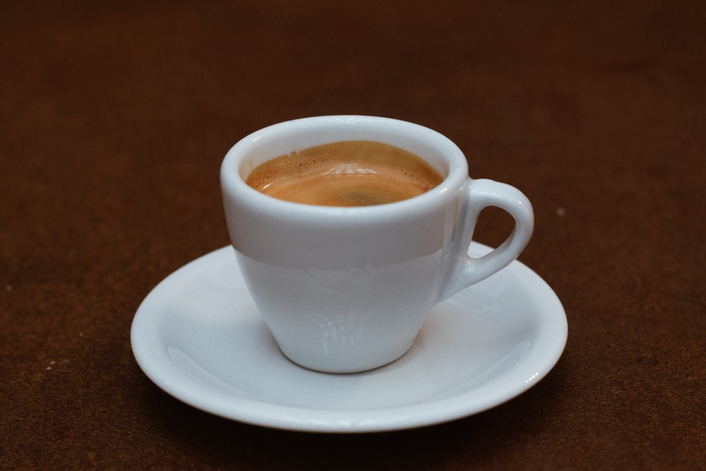 white ceramic teacup filled with brown coffee