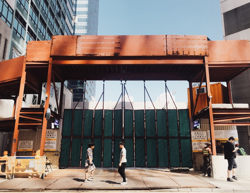 person walking in front of green steel gate