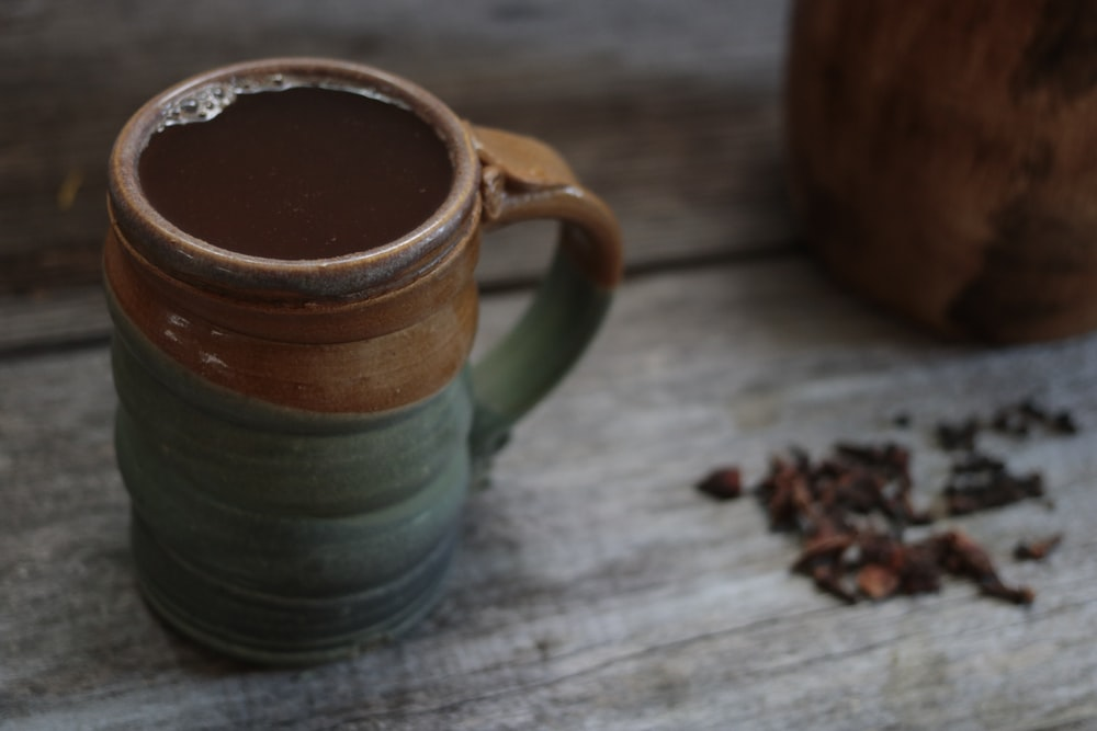 green and brown mug with water