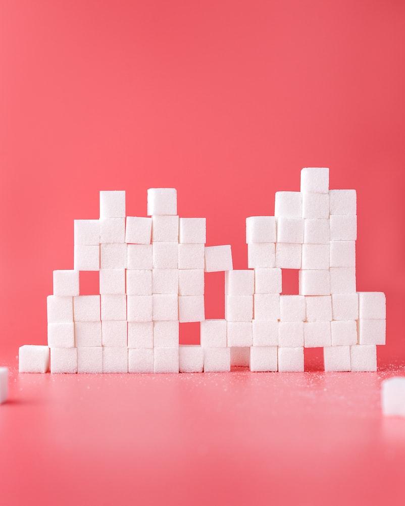 aufeinander gestapelter Zucker in Würfeln vor einem rotpinken Hintergrund