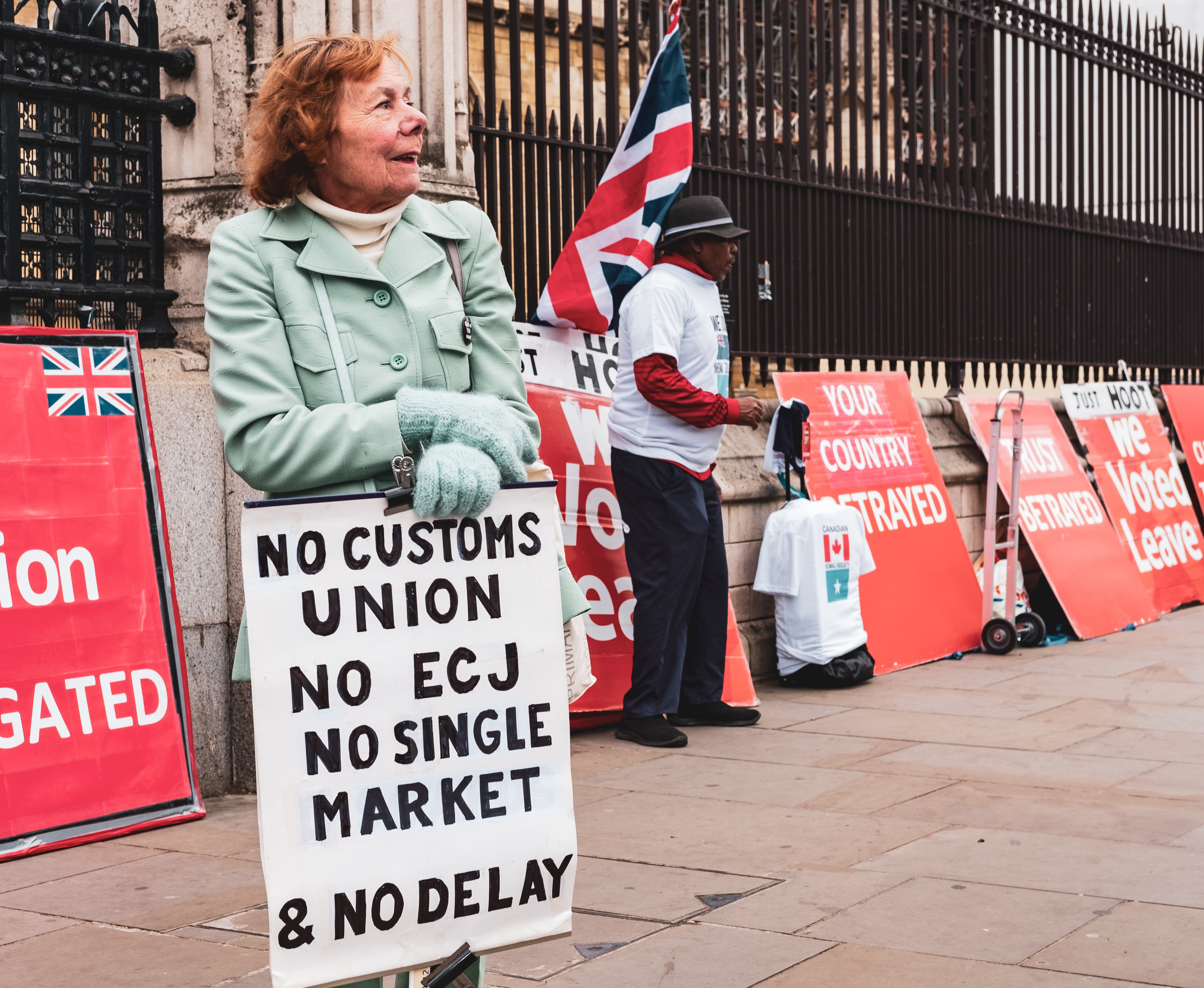 smiling woman holding No Customs Union No Ecj signage
