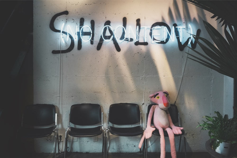 Pink Panther plush toy sitting under shallow sign