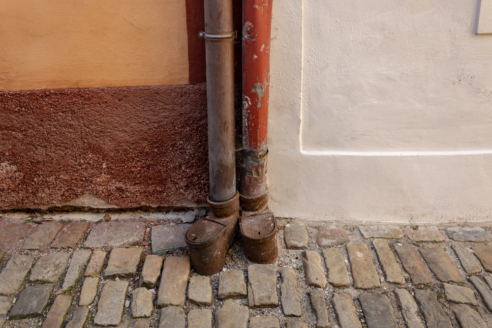two brown pipes beside wall