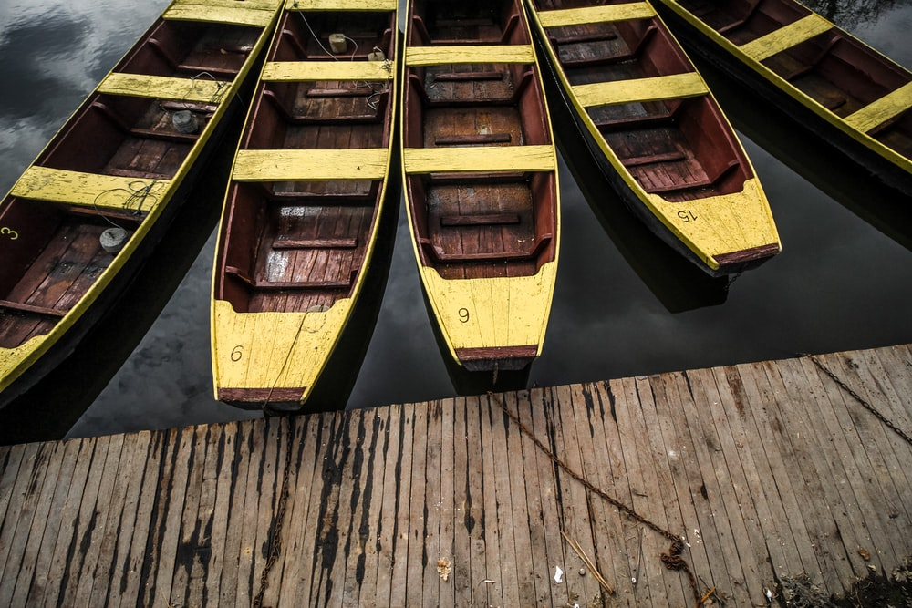 five brown-and-beige boats near dock
