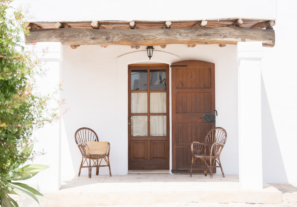 two brown rattan armchairs near door