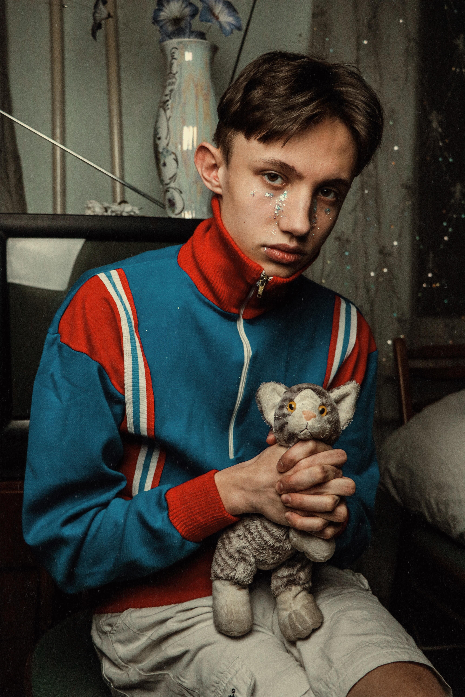 man holding gray feline plush toy
