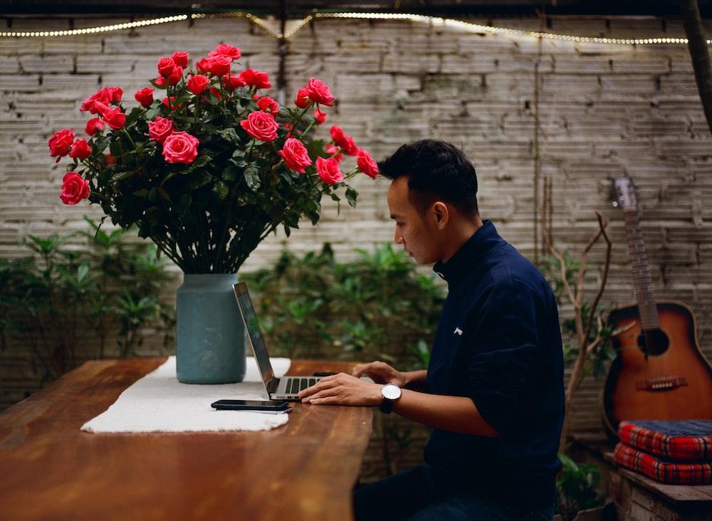 man sitting on chair using laptop